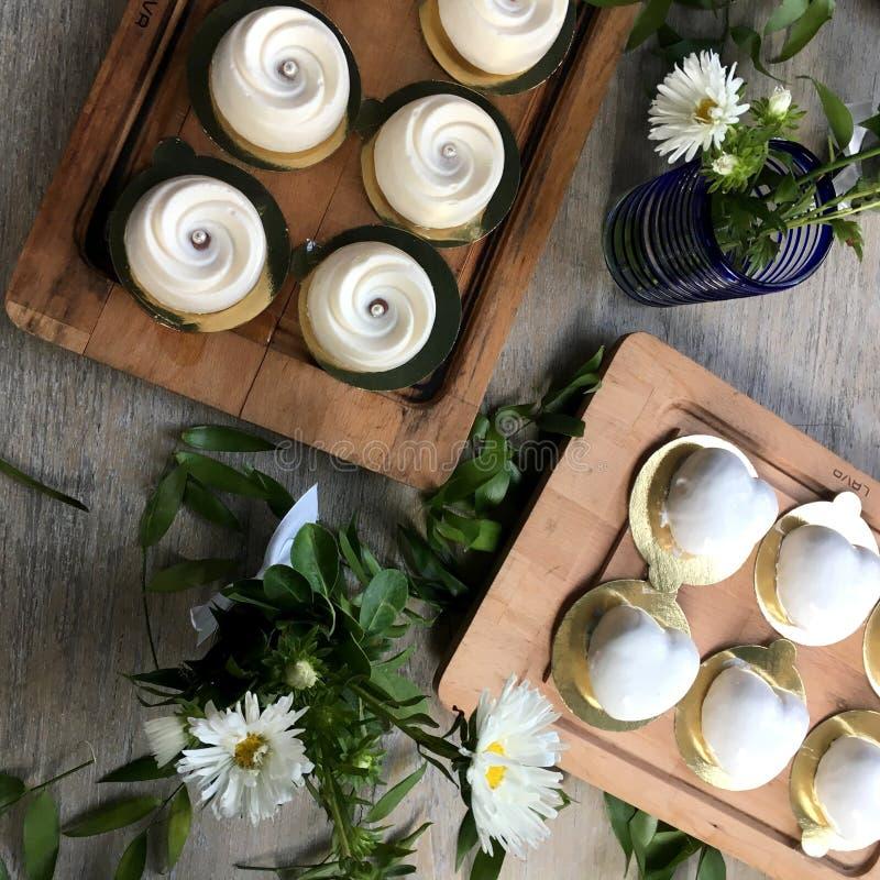 Galletas, magdalena, chocolate y flores blancas imagenes de archivo