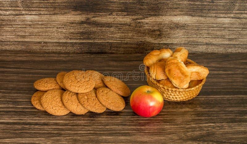 Galletas, manzana y cruasanes foto de archivo