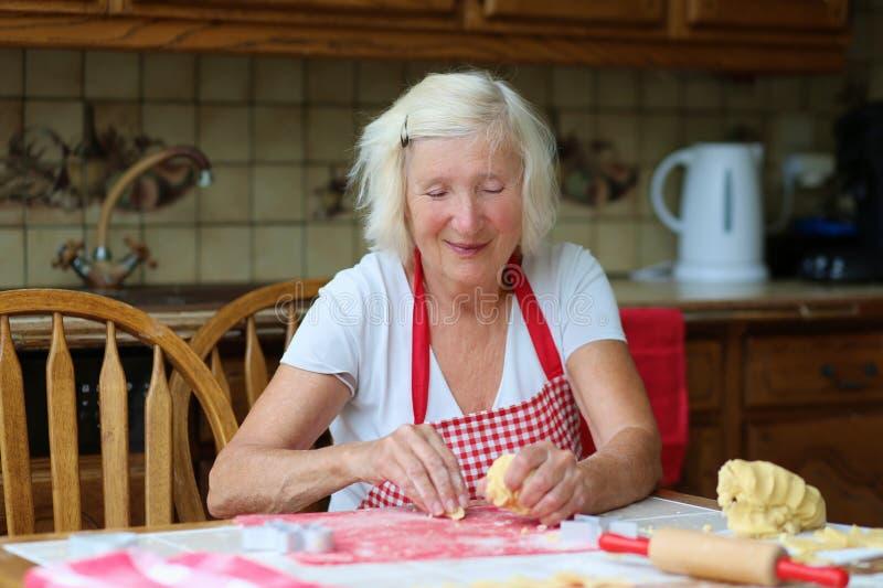 Galletas mayores felices de la hornada de la mujer en la cocina imágenes de archivo libres de regalías