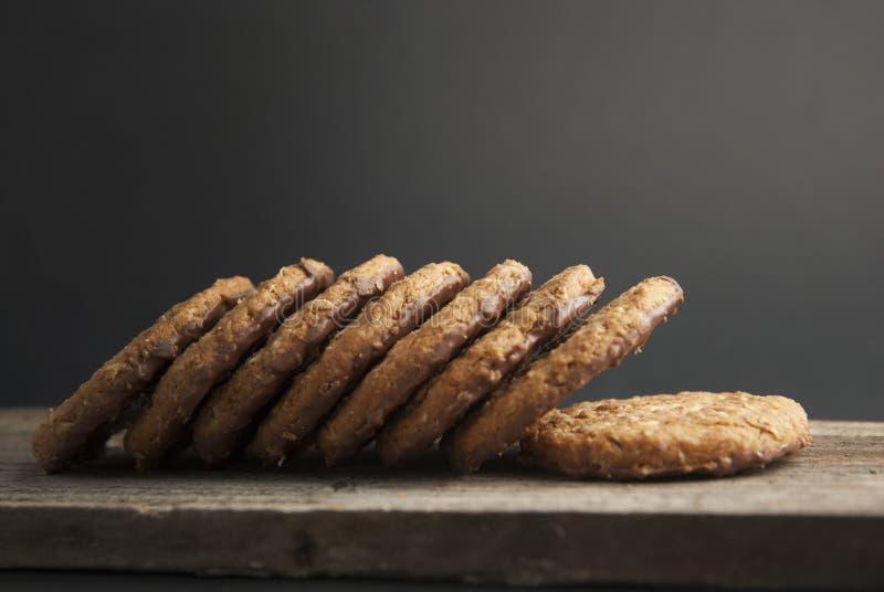 Galletas o galletas de harina de avena con la avena, las nueces, los huevos y la harina en woodenboard oscuro marrón con el fondo imagen de archivo