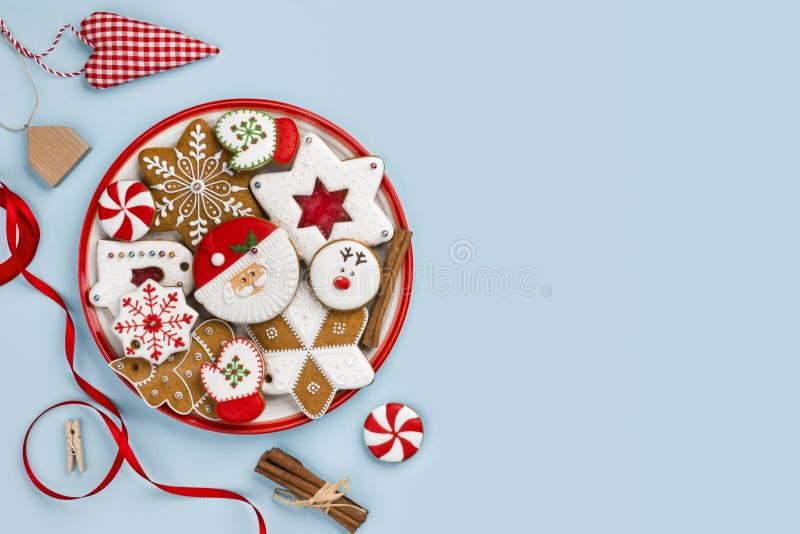 Galletas pintadas del pan de jengibre y decoración de la Navidad aislada en fondo azul fotos de archivo libres de regalías