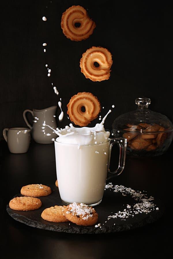 Galletas que caen al vidrio de leche con el chapoteo en fondo negro imagen de archivo