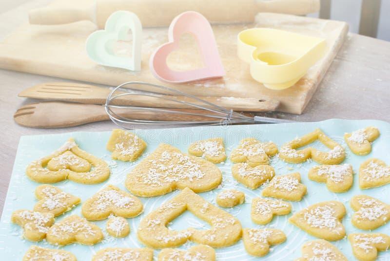 Galletas que mienten en un molde para el horno Utensilios en el fondo, formas de la cocina para las galletas, rodillo, batidor pr fotos de archivo libres de regalías