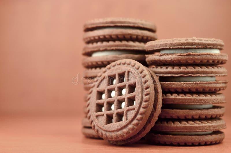 Galletas redondas del bocadillo del chocolate con el relleno poner crema de la vainilla en la tabla de madera marrón con el copys foto de archivo