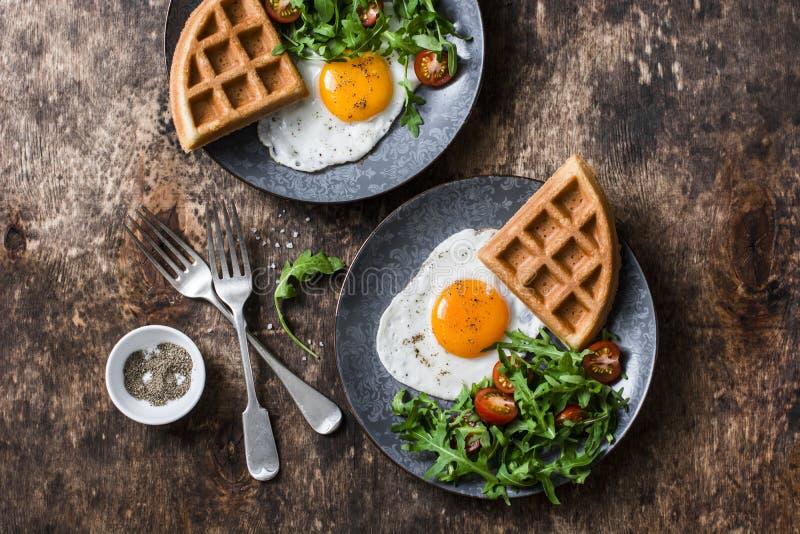 Galletas sabrosas, huevos fritos y arugula, ensalada del tomate de cereza - desayuno sano delicioso en fondo de madera fotografía de archivo