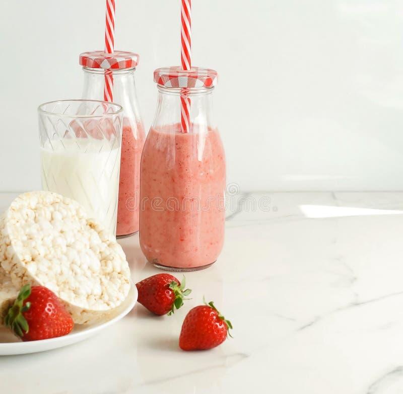 Galletas sanas del arroz como el desayuno, los bocados y las fresas frescas, los smoothies de la fresa y un vidrio de leche en la fotos de archivo