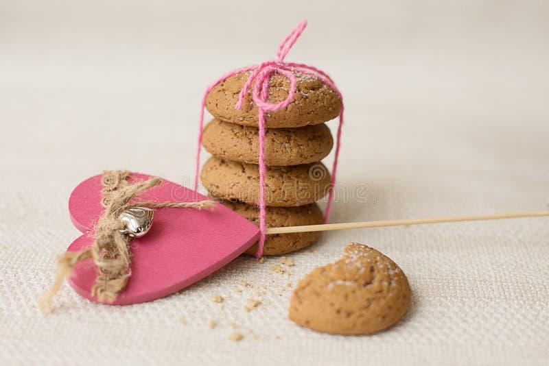 Galletas y corazón rosado en un fondo ligero fotografía de archivo libre de regalías