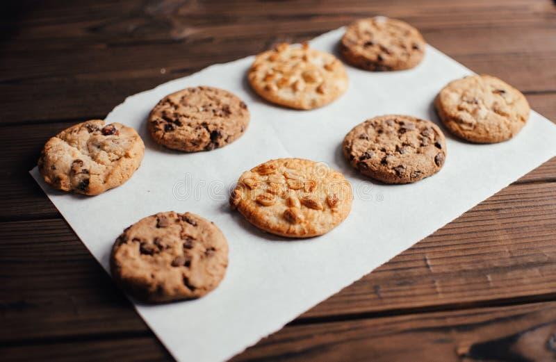Galletitas recubiertas de chocolate yacen en un papel perchado en una fila. Galletas sin gluten en una mesa de madera del horno. s imagenes de archivo