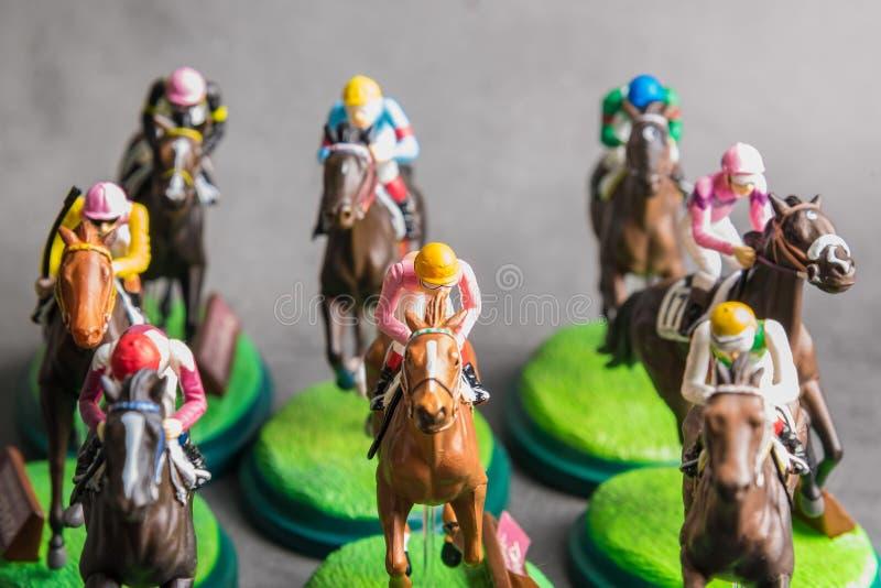 Galloping jinetes y caballos de carreras juguetes compitiendo por su posición Concepto de competir por la victoria imágenes de archivo libres de regalías