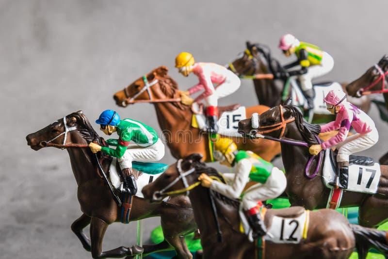 Galloping jinetes y caballos de carreras juguetes compitiendo por su posición Concepto de competir por la victoria imagen de archivo libre de regalías