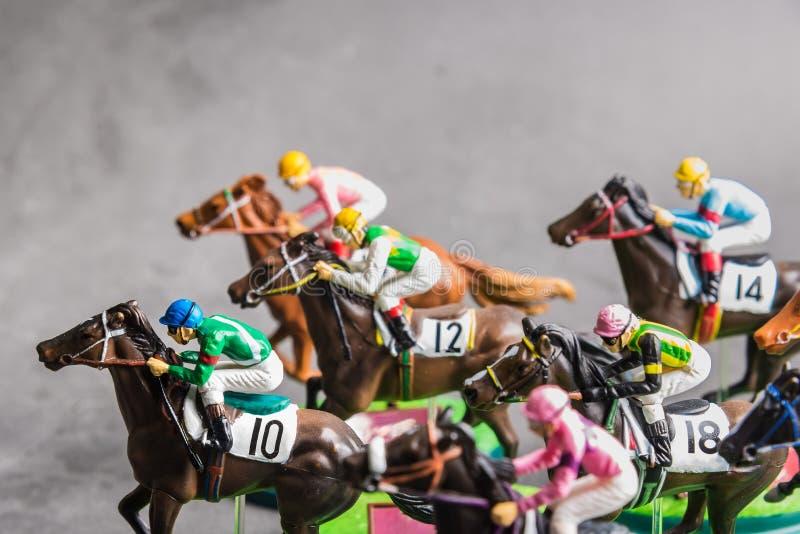 Galloping jinetes y caballos de carreras juguetes compitiendo por su posición Concepto de competir por la victoria fotos de archivo