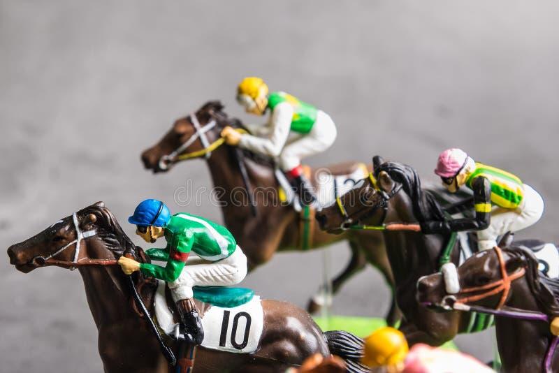 Galloping jinetes y caballos de carreras juguetes compitiendo por su posición Concepto de competir por la victoria imagen de archivo
