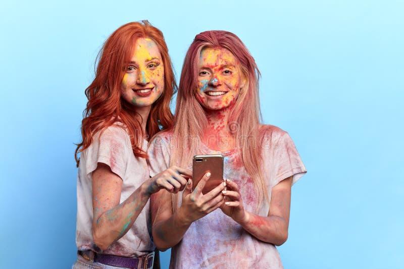 Galna roliga flickor med kulöra framsidor som rymmer smartphonen och poserar till kameran fotografering för bildbyråer