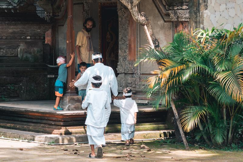 Galungan Holiday. A man with a child goes to the temple. The view from the back. Bali Island, Indonesia. 26.12.2018 royalty free stock image