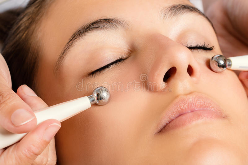 Galvanic facial treatment with low level current electrodes. Close up portrait of woman having Galvanic facial treatment with low level current electrodes stock photography