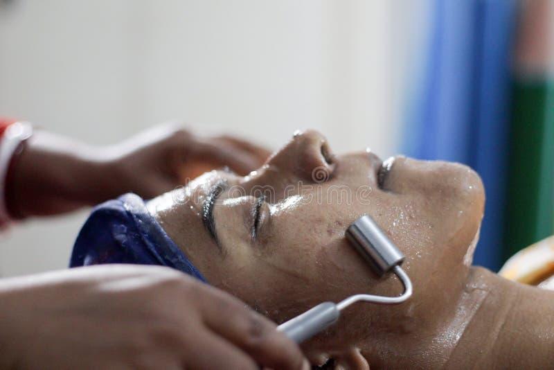 Galvanisationsanwendung auf Gesicht einer Dame mit Haarband mit Augen schloss Weicher Fokus stockfotografie