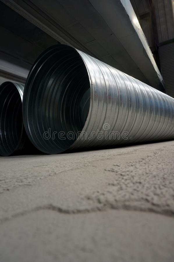 Galvanised steel ducting tubing for air extraction. On the floor of a factory warehouse stock photography