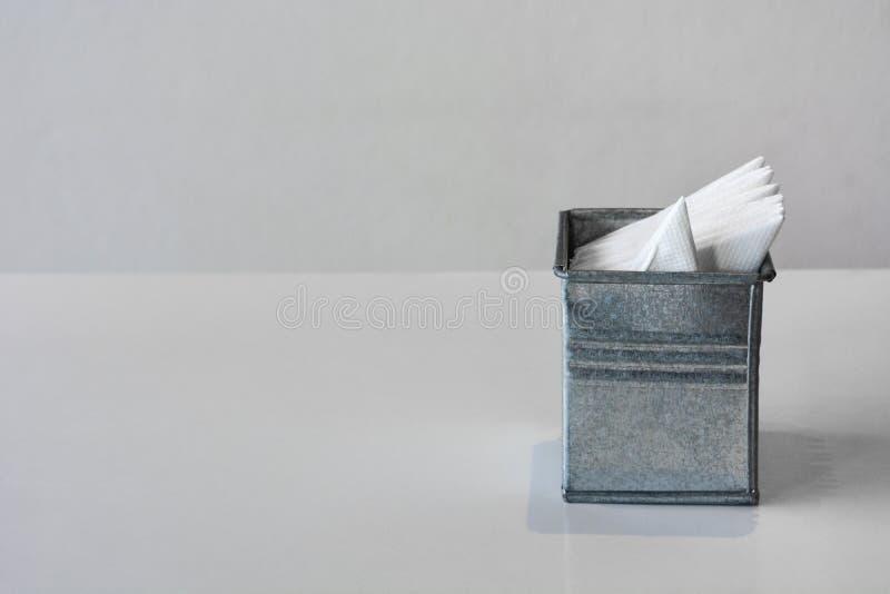 Galvaniserad eller zinksilkespapperask med den vikta servetten som är enkel att använda på tabellen, vit bakgrund fotografering för bildbyråer