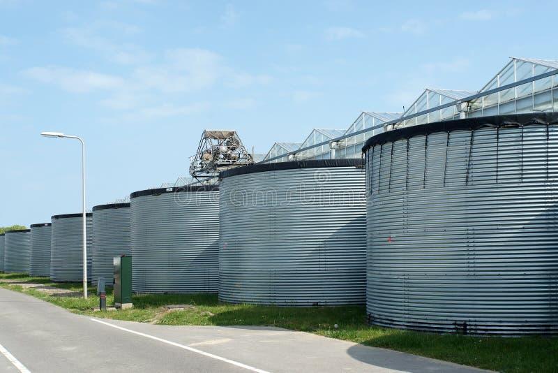 Galvanisierte Stahlsilos für Lagerung des Regenwassers nahe Gewächshaus lizenzfreie stockbilder