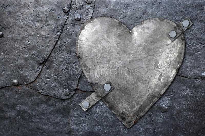Galvanized metal heart. Photo of a galvanized metal heart bolted to old hammered metal plates with rivets