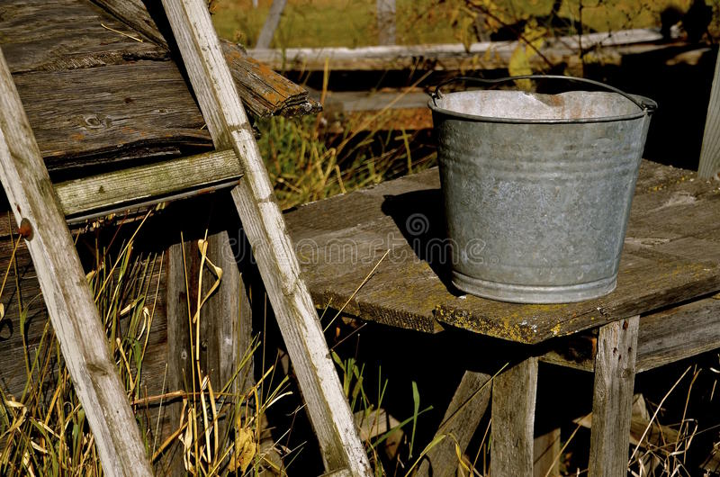 Galvanized pail rests on an old table. A galvanized pail rests on an old table alongside a wooden ladder stock photos