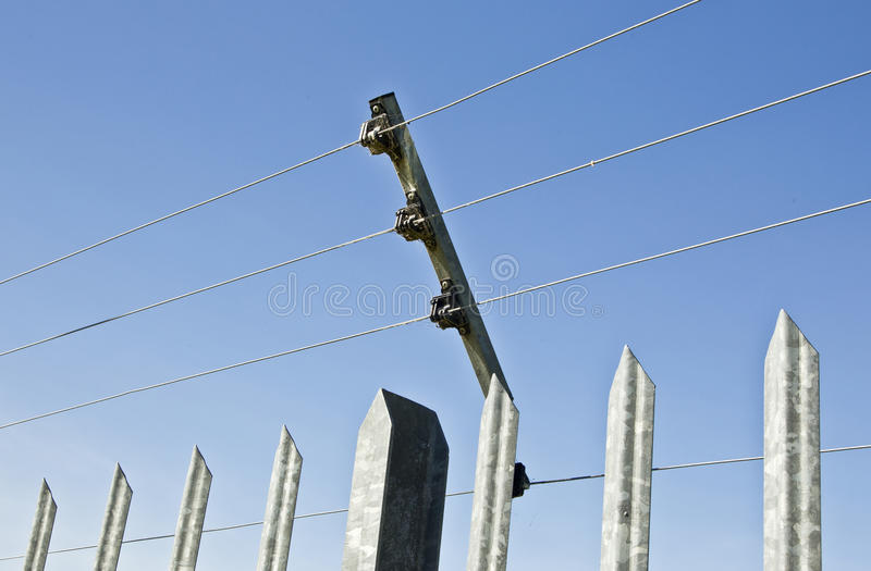 Galvanized poles holding a high voltage security fence royalty free stock photography