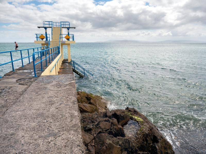 Galway / Ireland 02/20/2019 Blackrock public diving board, Boy jumping into water. High tide, Cloudy sky, Burren mountains in the stock photos