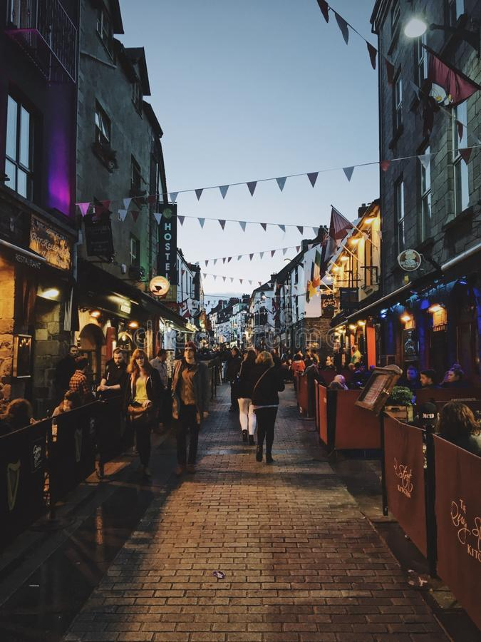 Streets of Galway, Ireland. GALWAY, IRELAND - Mar 09, 2018: A festive atmosphere on the streets of Galway with lots of cafes, bars, shops, and rustic decor royalty free stock photos