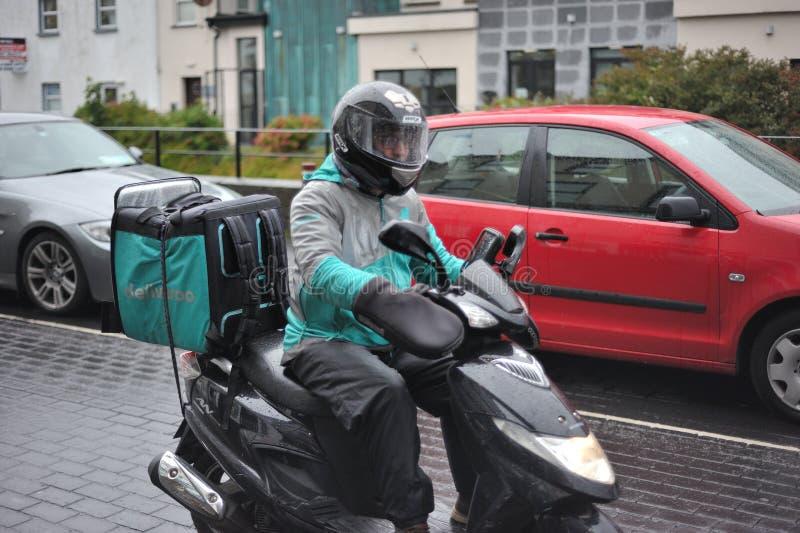 Galway, Irland im Juni 2017, Deliveroo-Kerl, der eine Lieferung in einem s macht stockfotografie