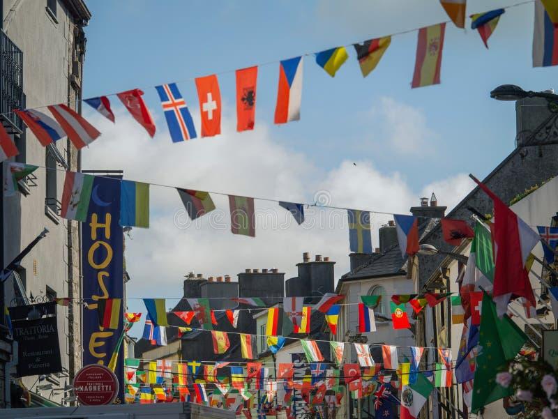 07/03/2019 Galway stad, Irland Färgrika internationella flaggor som hänger över, shoppar gatan bl? molnig sky royaltyfri fotografi