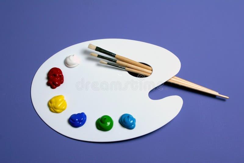 Gama de colores de la pintura del artista con las pinturas y los cepillos, simbólicos de arte imagenes de archivo