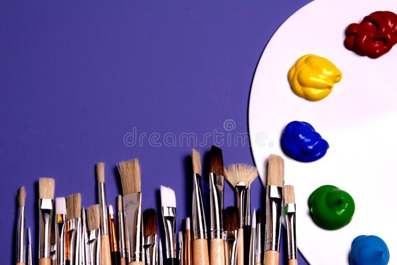 Gama de colores de la pintura del artista con las pinturas y los cepillos, simbólicos de arte foto de archivo libre de regalías
