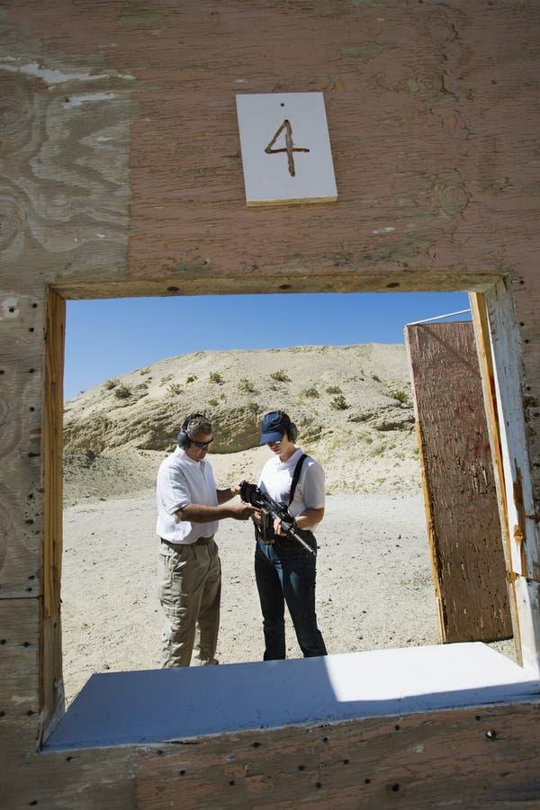 Gama de leña de Assisting Woman At del instructor en desierto fotos de archivo libres de regalías
