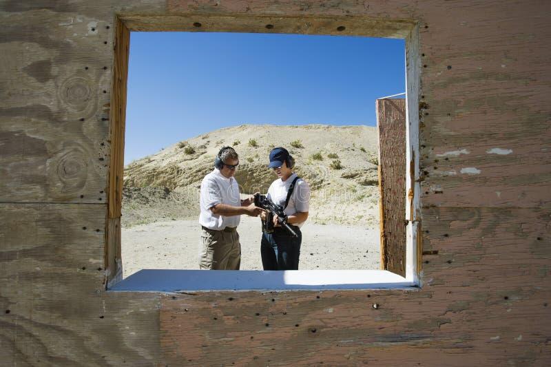 Gama de leña de Assisting Woman At del instructor en desierto imágenes de archivo libres de regalías