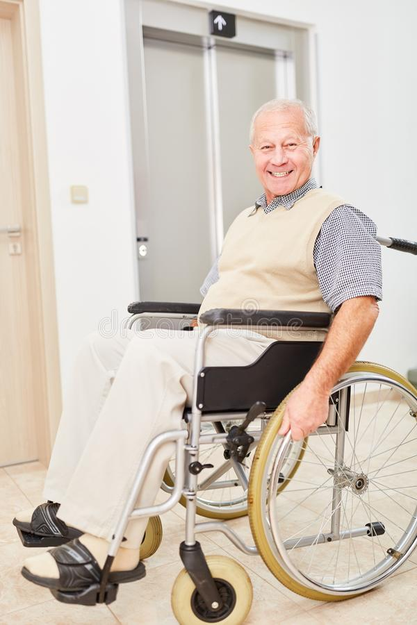 Gamal man i en rullstol framme av en elevator arkivbild