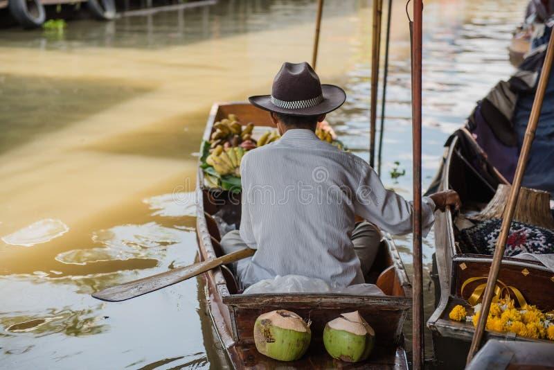Gamal man i fartyg Damnoen Saduak som svävar marknaden i Ratchaburi nära Bangkok, Thailand fotografering för bildbyråer