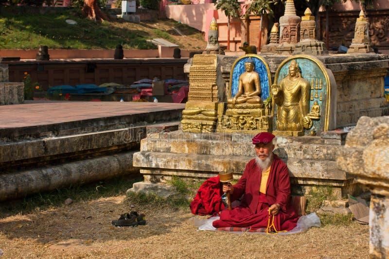 Gamal man i klänning av sammanträde och att be för munk royaltyfria foton