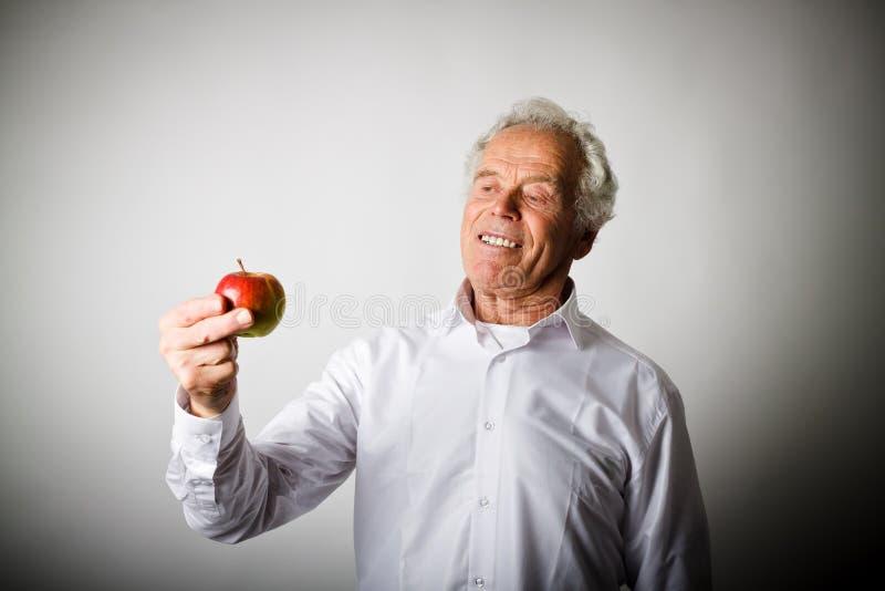 Gamal man i vit och äpple arkivfoton