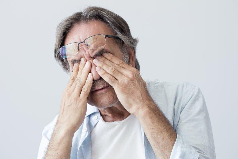 Gamal man med ögontrötthet arkivfoton