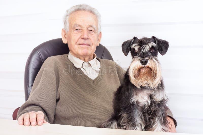 Gamal man med den svarta miniatyrSchnauzerhunden arkivbilder