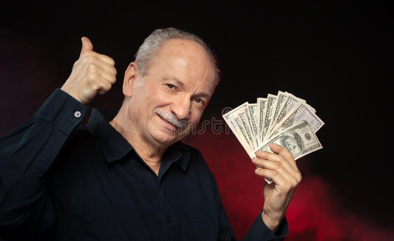 Gamal man med dollarbills arkivbilder