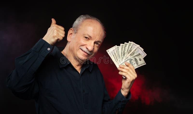 Gamal man med dollarbills arkivfoton