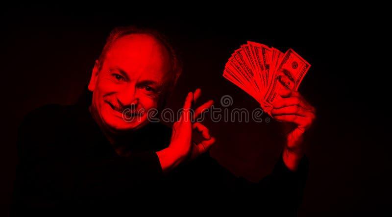 Gamal man med dollarbills arkivbild