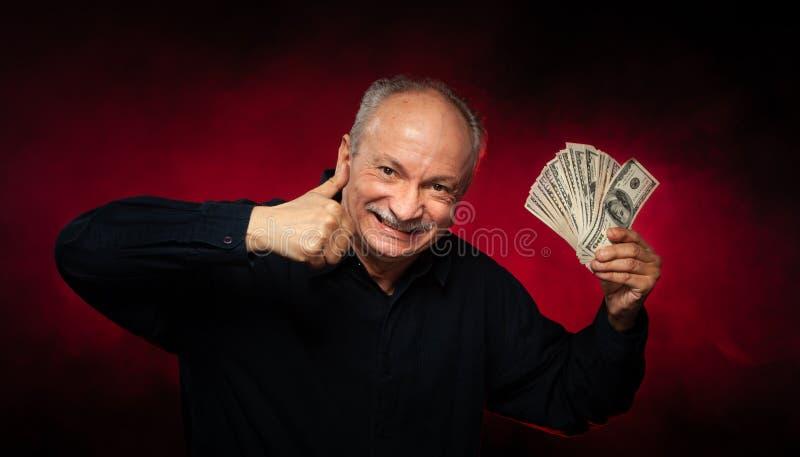 Gamal man med dollarbills royaltyfria foton