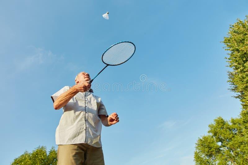 Gamal man med fjäderboll och racket arkivfoton