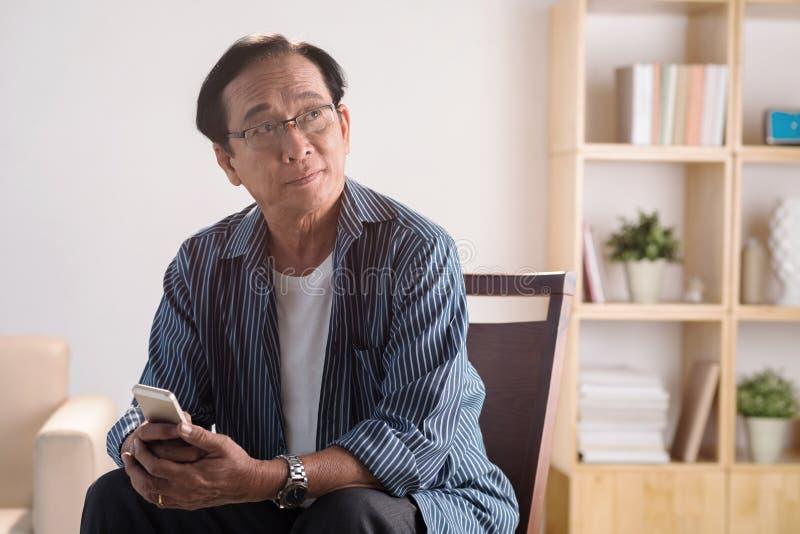 Gamal man med telefonen arkivbilder