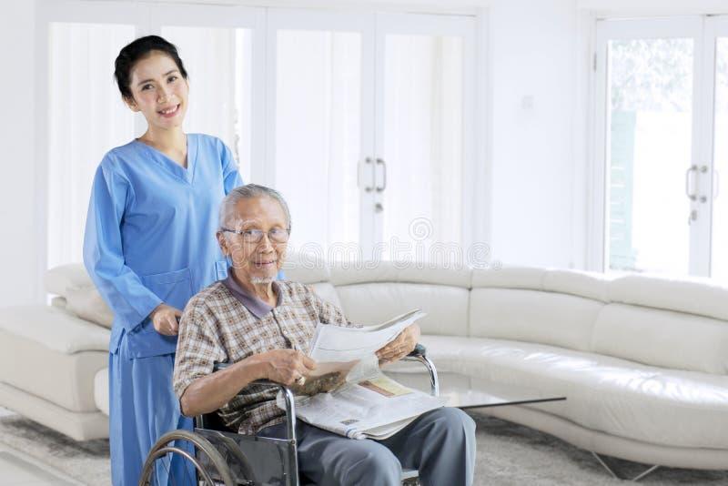 Gamal man och hans sjuksköterska som ler på kameran arkivfoto