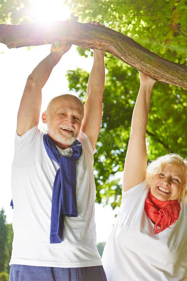 Gamal man och kvinna som gör sportar i natur arkivbild
