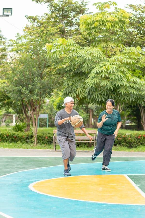 Gamal man och kvinna som så lyckligt spelar basket i morgonen arkivbild
