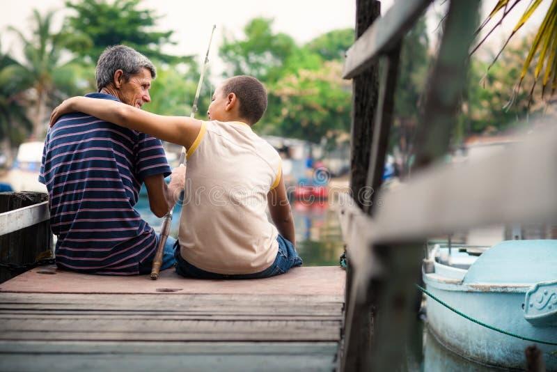 Gamal man- och pojkefiske tillsammans på floden för gyckel royaltyfria bilder